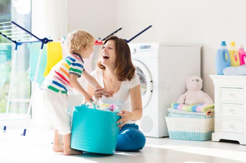 Famiglia nella stanza di lavanderia con la lavatrice fotografia stock