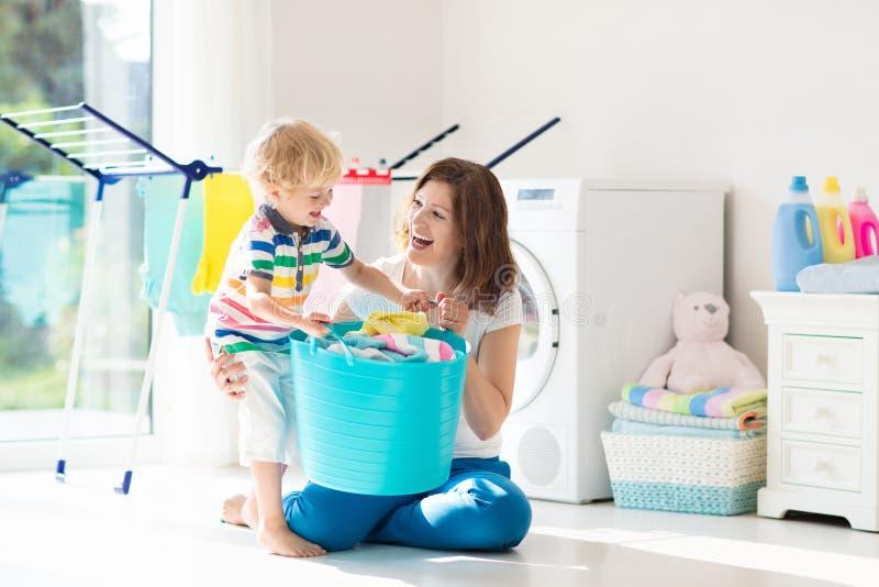 Famiglia nella stanza di lavanderia con la lavatrice fotografia stock libera da diritti