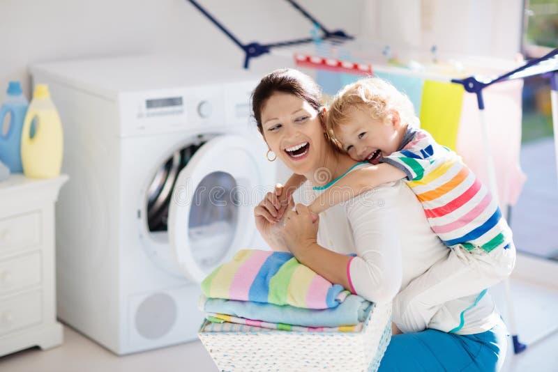 Famiglia nella stanza di lavanderia con la lavatrice immagine stock