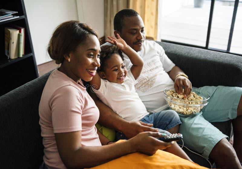 Famiglia nera che mangia popcorn mentre guardando film a casa immagini stock libere da diritti