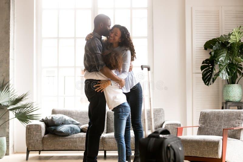Famiglia nera felice che abbraccia accogliendo favorevolmente papà africano h di ritorno immagine stock libera da diritti