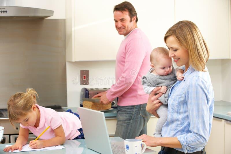 Famiglia occupata insieme in cucina immagini stock