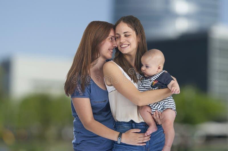 Famiglia omosessuale, giovani madri lesbiche con il loro bambino Amore lesbico immagini stock