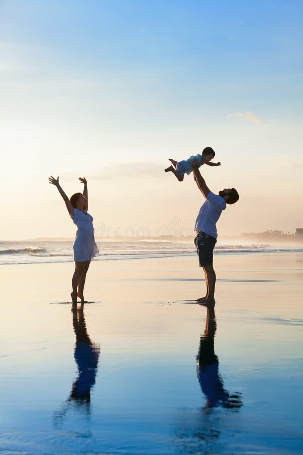 Famiglia - padre, madre, passeggiata del bambino sulla spiaggia di tramonto fotografie stock libere da diritti