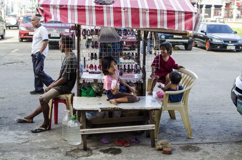 Famiglia povera che vive nelle vie che vendono le candele ed olio medicinale fotografia stock