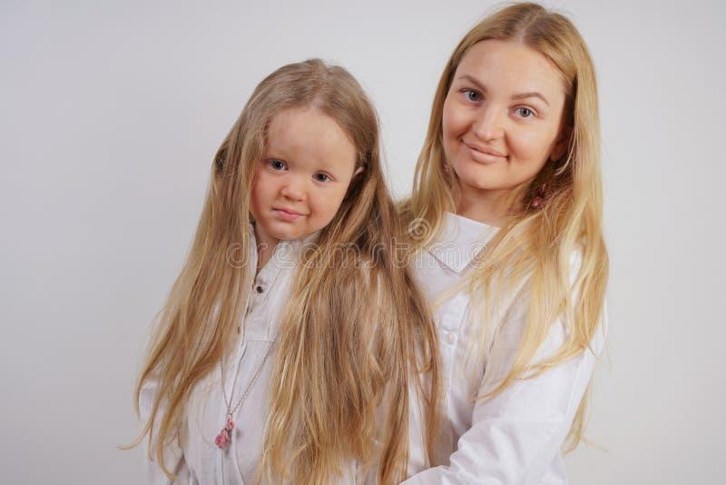 Famiglia reale della madre e della figlia caucasiche in camice bianche nei precedenti dello studio immagine stock libera da diritti