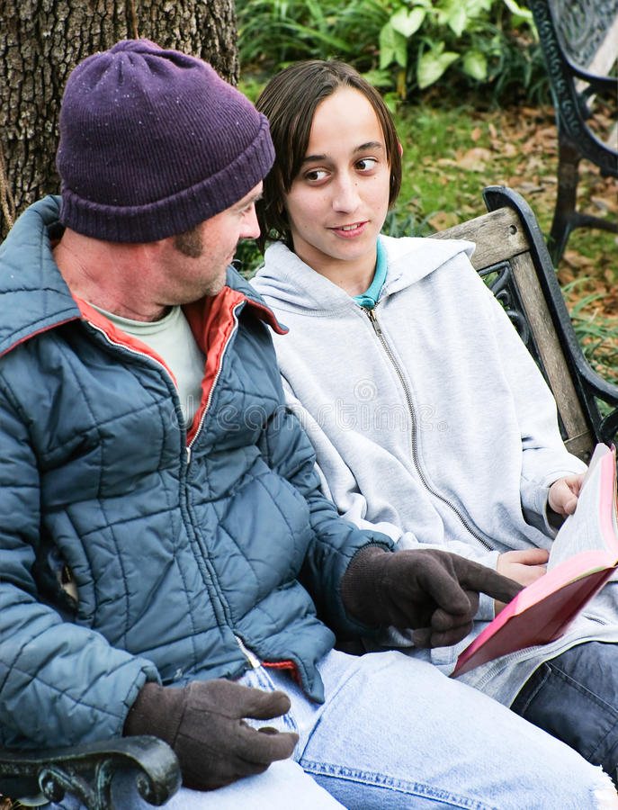 Famiglia senza tetto con la bibbia immagine stock