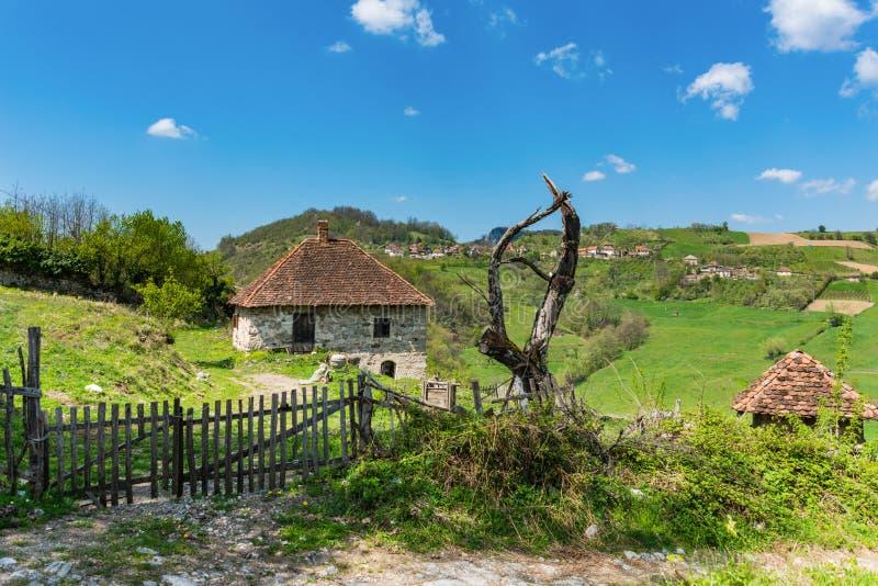 Famiglia serba sulla montagna Casa del villaggio e recinto di legno immagini stock