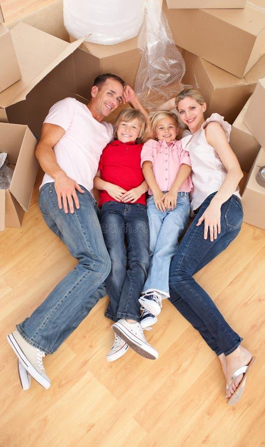 Famiglia sorridente che si trova sul pavimento immagine stock libera da diritti