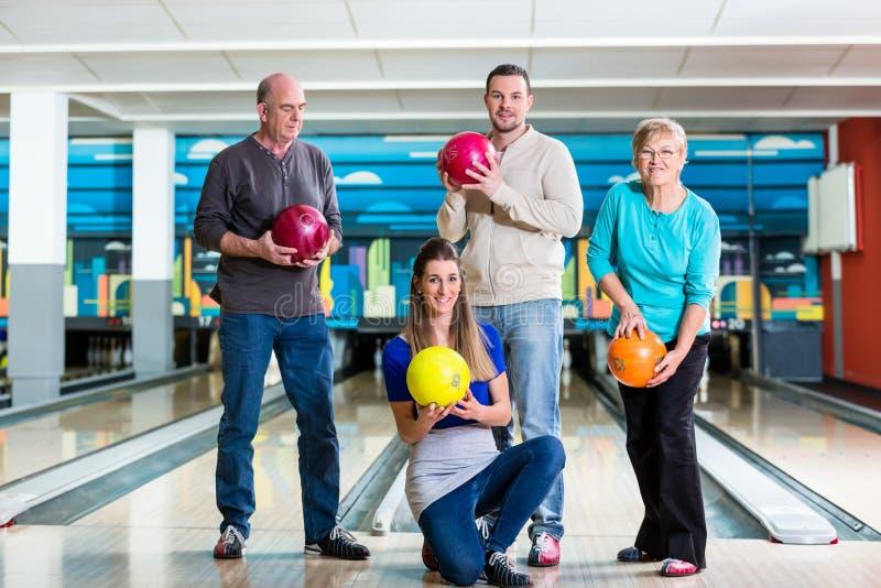 Famiglia sorridente che tiene palla da bowling fotografia stock