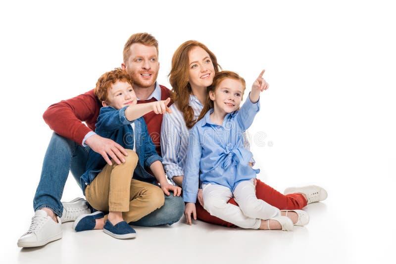 famiglia sorridente con due bambini che indicano via con le dita fotografia stock libera da diritti