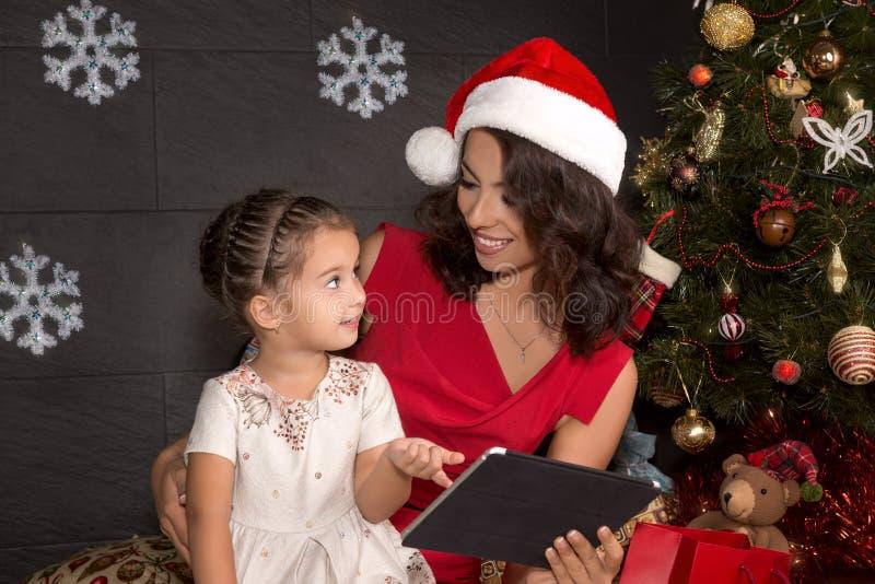 Famiglia sorridente con il pc della compressa Tempo di natale immagini stock libere da diritti
