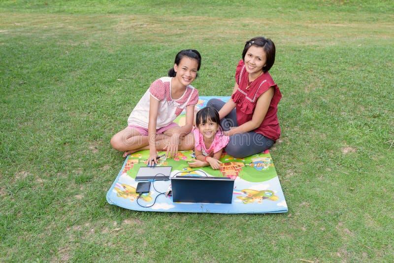 Famiglia sorridente facendo uso del computer portatile all'aperto fotografia stock