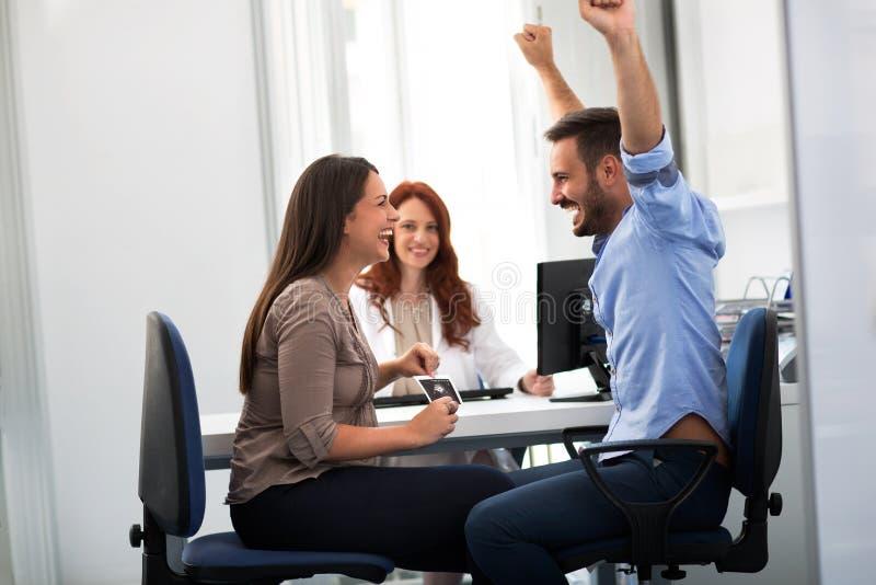Famiglia sorridente felice alla clinica del ginecologo immagine stock