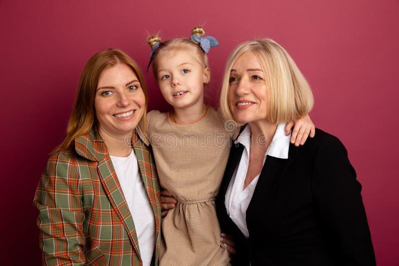 Famiglia sorridente felice di Portraitof Bambino con la mamma e la nonna in uno studio fotografie stock
