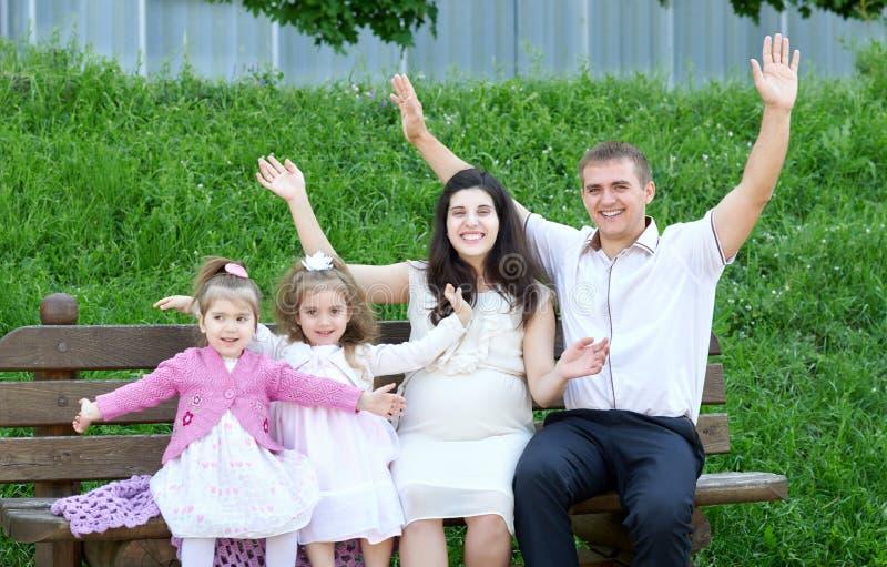 Famiglia su all'aperto a braccia aperte, donna incinta con il bambino e l'uomo, parco della città, stagione estiva, erba verde ed fotografia stock