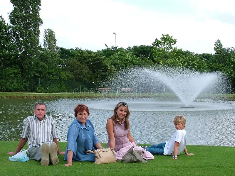 Famiglia su un'erba sotto il cielo blu immagine stock libera da diritti
