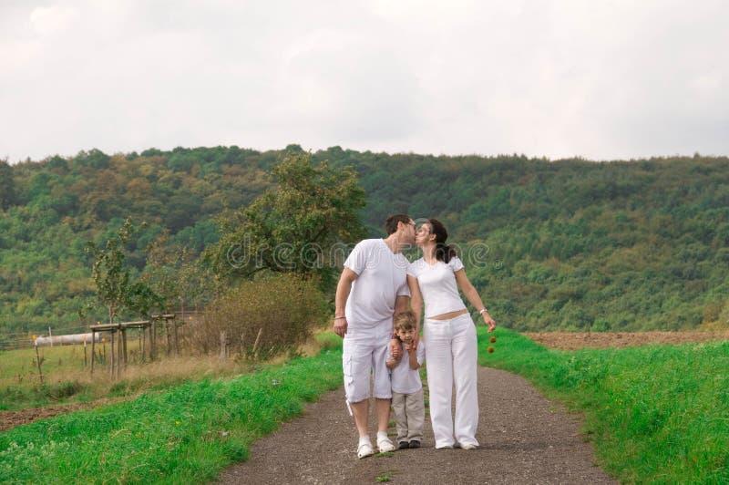 Famiglia su una passeggiata. Bacio. immagini stock libere da diritti