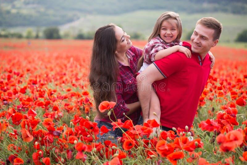 Famiglia sul campo del papavero immagini stock
