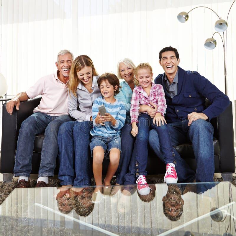 Famiglia sul sofà che guarda Smart TV immagine stock