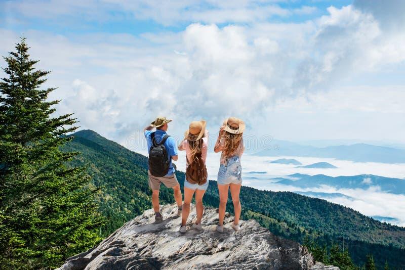 Famiglia sull'escursione del viaggio, stante sopra la montagna sopra le nuvole fotografia stock libera da diritti