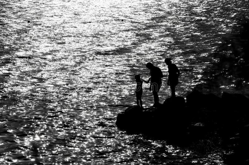Famiglia sulla costa rocciosa immagine stock