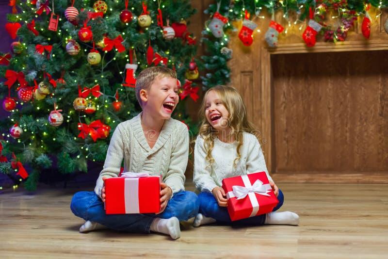 Famiglia sulla notte di Natale al camino Bambini che aprono i presente di natale fotografia stock libera da diritti