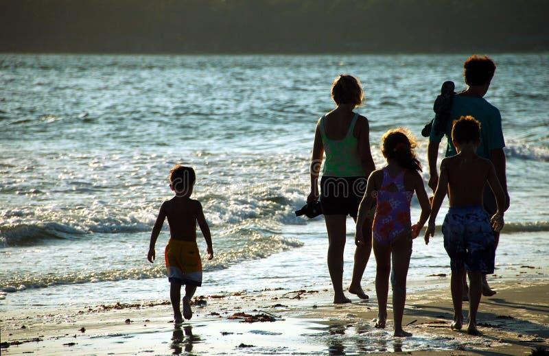 Famiglia sulla spiaggia al tramonto immagine stock