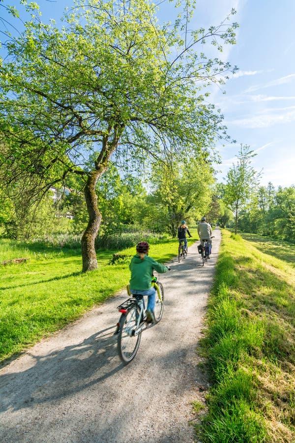 Famiglia sulle bici nel paesaggio scenico della molla immagine stock libera da diritti
