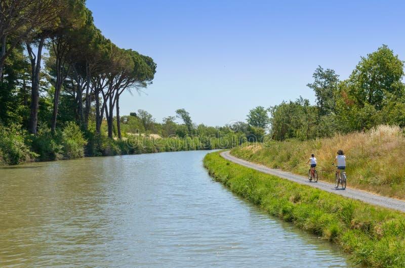Famiglia sulle bici, sulla madre e sulla figlia ciclanti dal canale du Midi, vacanze estive in Francia fotografia stock libera da diritti