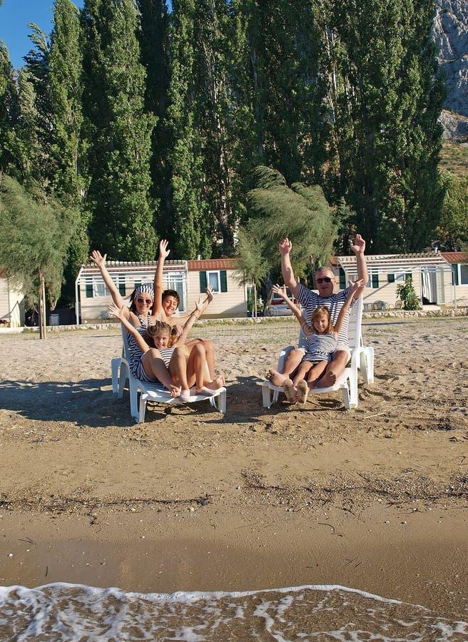 Famiglia sulle presidenze di piattaforma alla spiaggia 2 della sabbia immagine stock