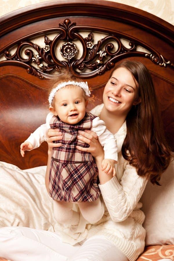 Famiglia sveglia nella camera da letto Madre e figlia nell'interno immagine stock libera da diritti