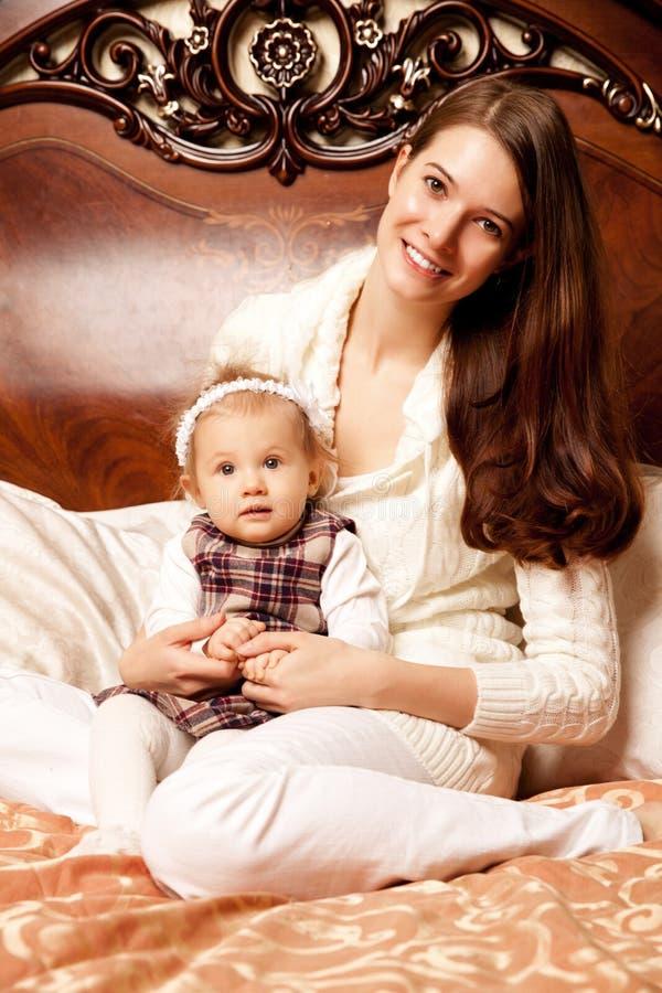 Famiglia sveglia nella camera da letto Madre e figlia nell'interno fotografia stock