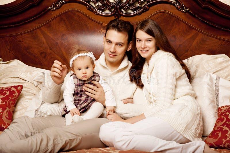 Famiglia sveglia nella camera da letto Madre, padre e figlia nella i fotografia stock