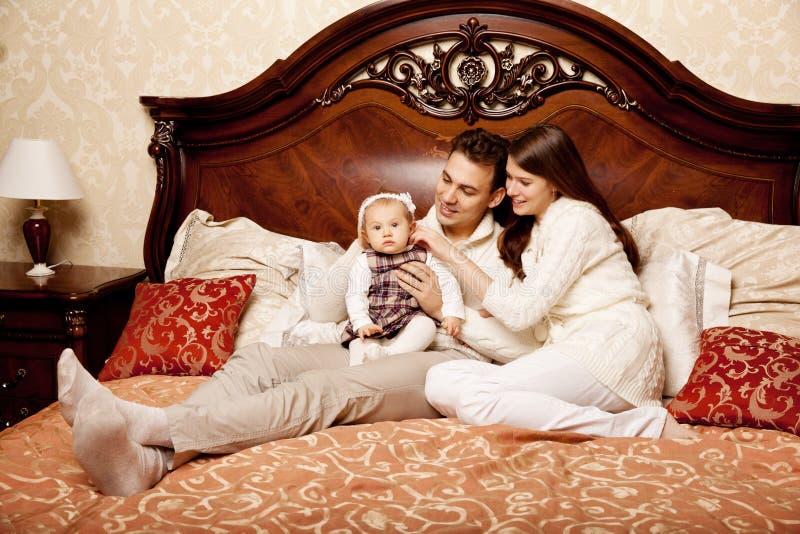 Famiglia sveglia nella camera da letto Madre, padre e figlia nella i immagini stock
