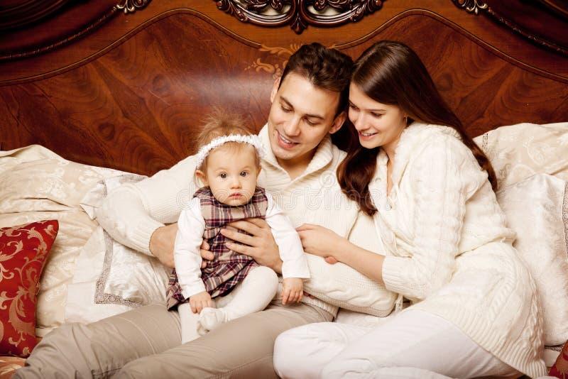 Famiglia sveglia nella camera da letto Madre, padre e figlia nella i fotografia stock libera da diritti