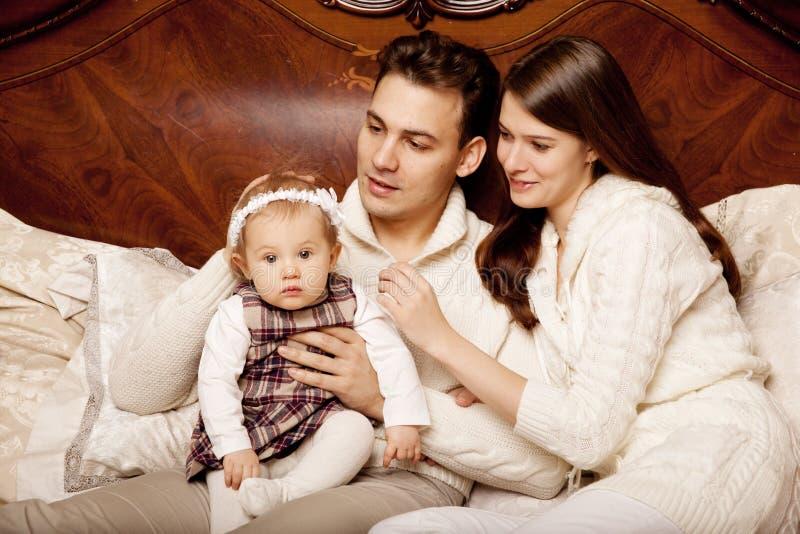 Famiglia sveglia nella camera da letto Madre, padre e figlia nella i fotografie stock