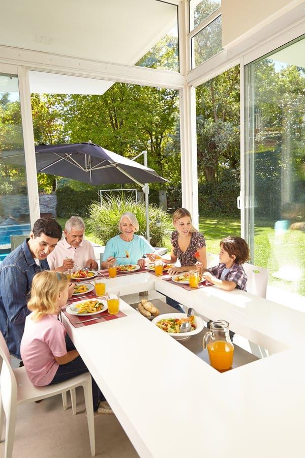 Famiglia in tre generazioni che mangiano alla tavola del pranzo fotografia stock