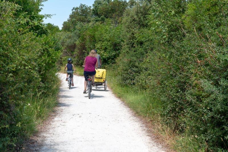 Famiglia turistica in bicicletta durante le vacanze padre e figli pedalano nell'isola di ile d'Aix Charente fotografia stock libera da diritti