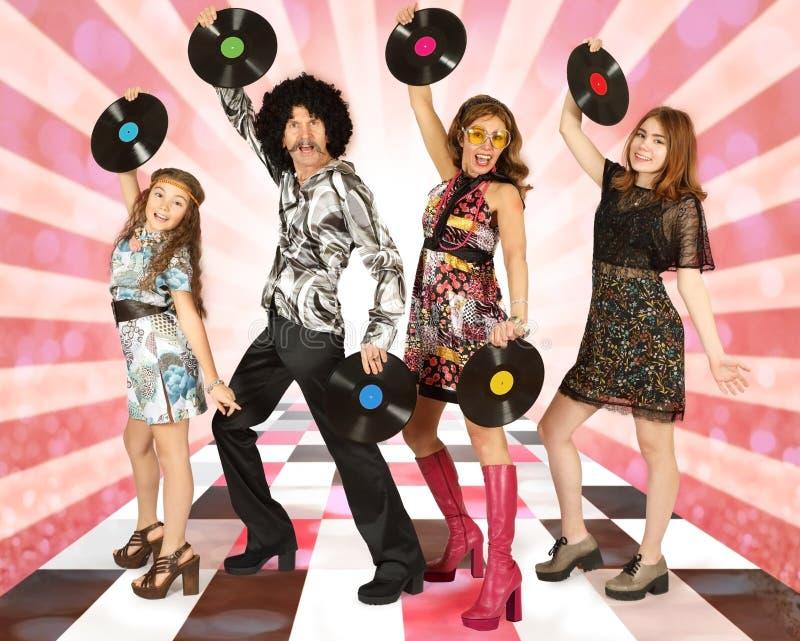 Famiglia vestita nello stile della discoteca con le annotazioni di vinile fotografia stock