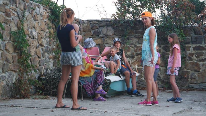 Famiglie felici con i bambini in cortile vicino alla barca di mare fotografie stock