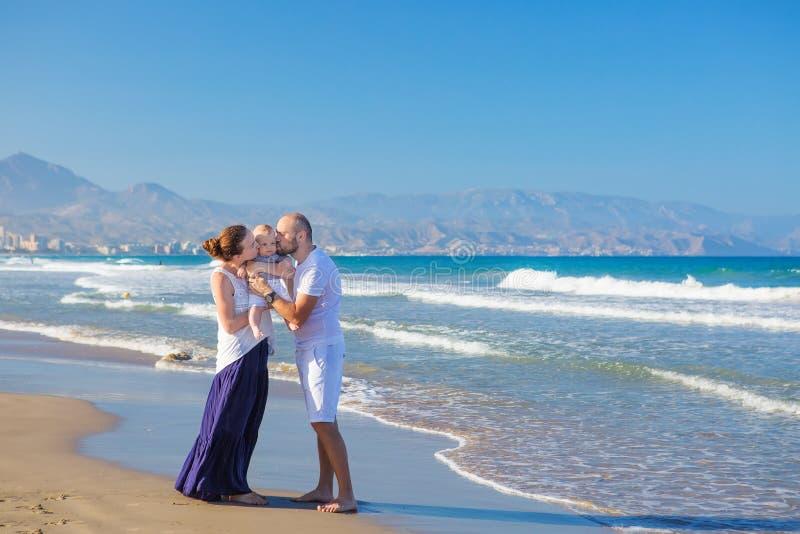 FamilFamily zabawę przy denną plażą przy sunsety mieć zabawę przy obraz royalty free