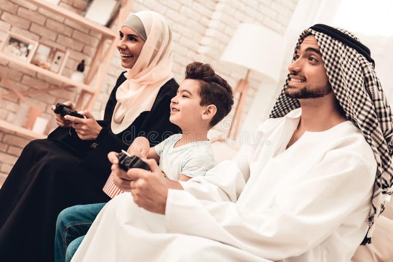 Familia árabe feliz que juega en la consola en casa imagen de archivo