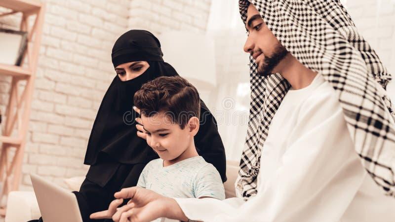 Familia árabe joven usando el ordenador portátil en el sofá en casa imágenes de archivo libres de regalías