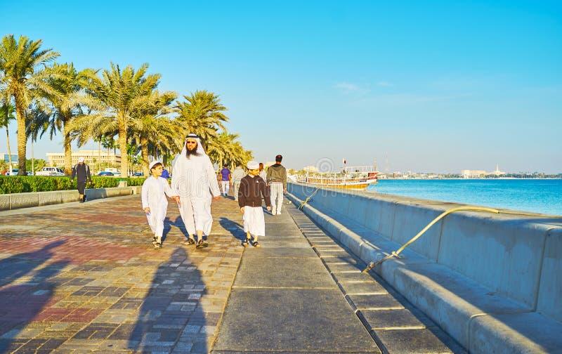 Familia árabe que camina en Doha, Qatar foto de archivo