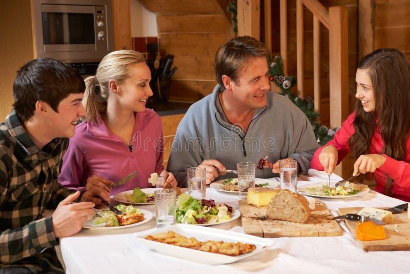 Familia adolescente que disfruta de la comida en chalet alpestre imagenes de archivo