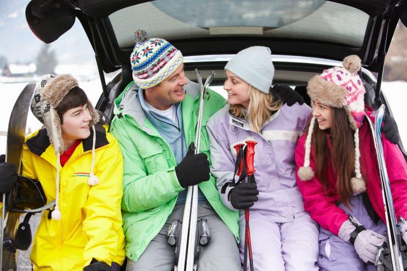 Familia adolescente que se sienta en el cargador del programa inicial del coche con los esquís foto de archivo