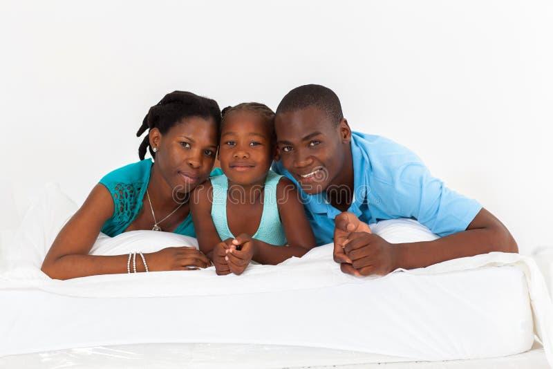 Familia africana en cama imagen de archivo libre de regalías