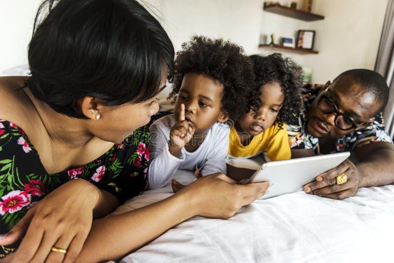 Familia africana en cama usando una tableta imagen de archivo