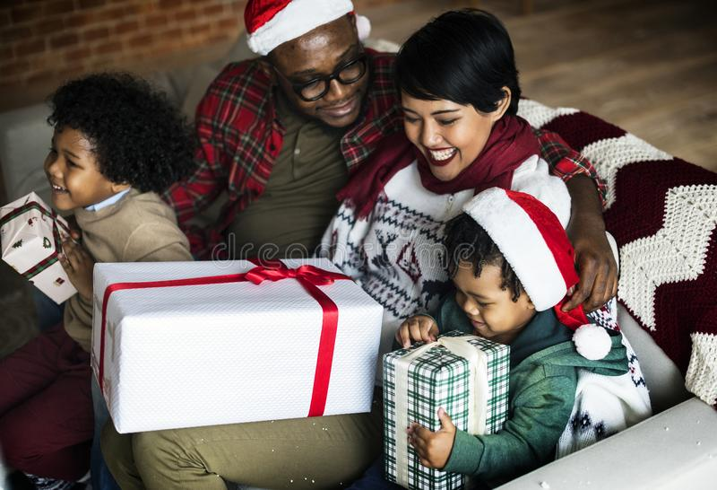 Familia africana feliz que celebra con los regalos de la Navidad imagen de archivo